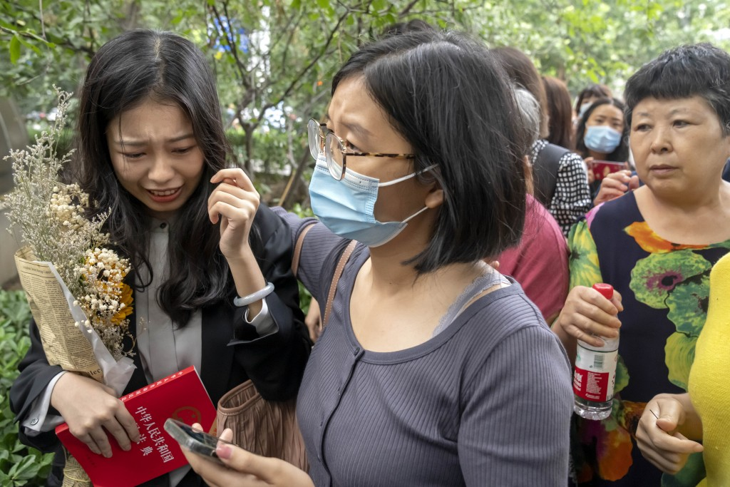 Zhou Xiaoxuan, left, a former intern at China's state broadcaster CCTV, reacts after being accosted by hostile bystanders outside a courthouse in Beij...