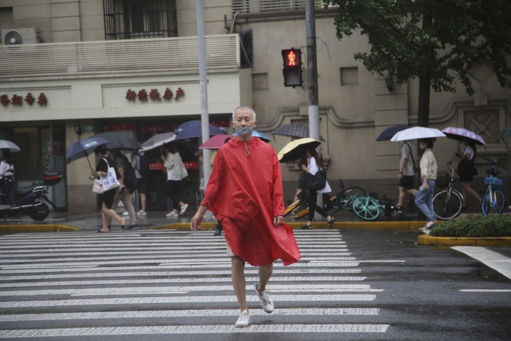 A resident wearing a mask and rain gear crosses the road in Shanghai, China, Tuesday, Sept. 14, 2021. Flights and train service were being canceled in...