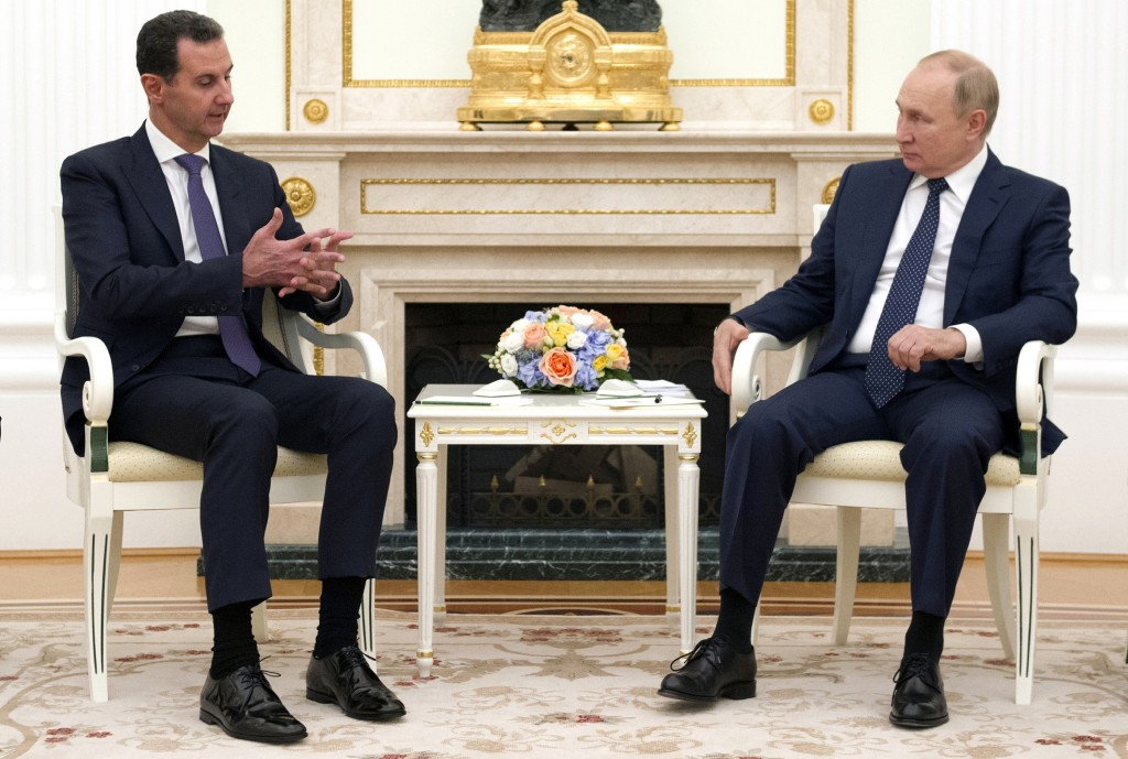 Russian President Vladimir Putin, right, sits with Syrian President Bashar Assad during their meeting in the Kremlin in Moscow, Russia, Monday, Sept. ...