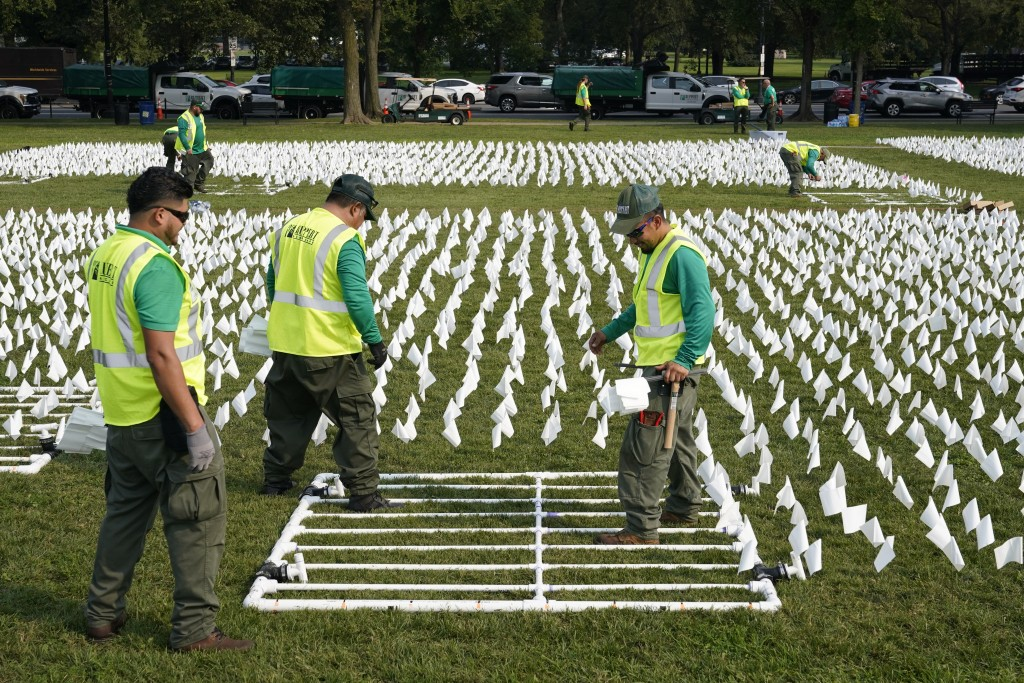 """Workers plant white flags as part of artist Suzanne Brennan Firstenberg's temporary art installation, """"In America: Remember,"""" in remembrance of Americ..."""