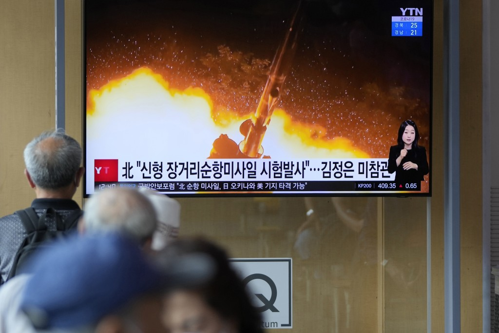 """People watch a news program that was showing part of a North Korean handout photo that says, """"North Korea's long-range cruise missiles tests,"""" in Seou..."""