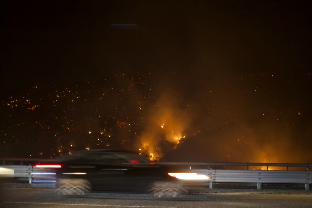 A vehicle drives on Interstate 5 south bound past the burning Route fire, a brush wildfire off Interstate 5 north of Castaic, Calif., on Saturday, Sep...
