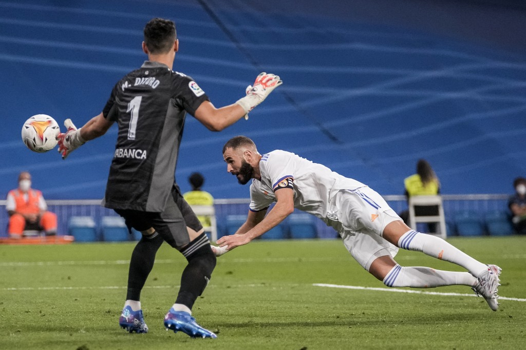 Real Madrid's Karim Benzema, right, heads for the ball next to Celta Vigo's goalkeeper Matias Dituro during the Spanish La Liga soccer match between R...