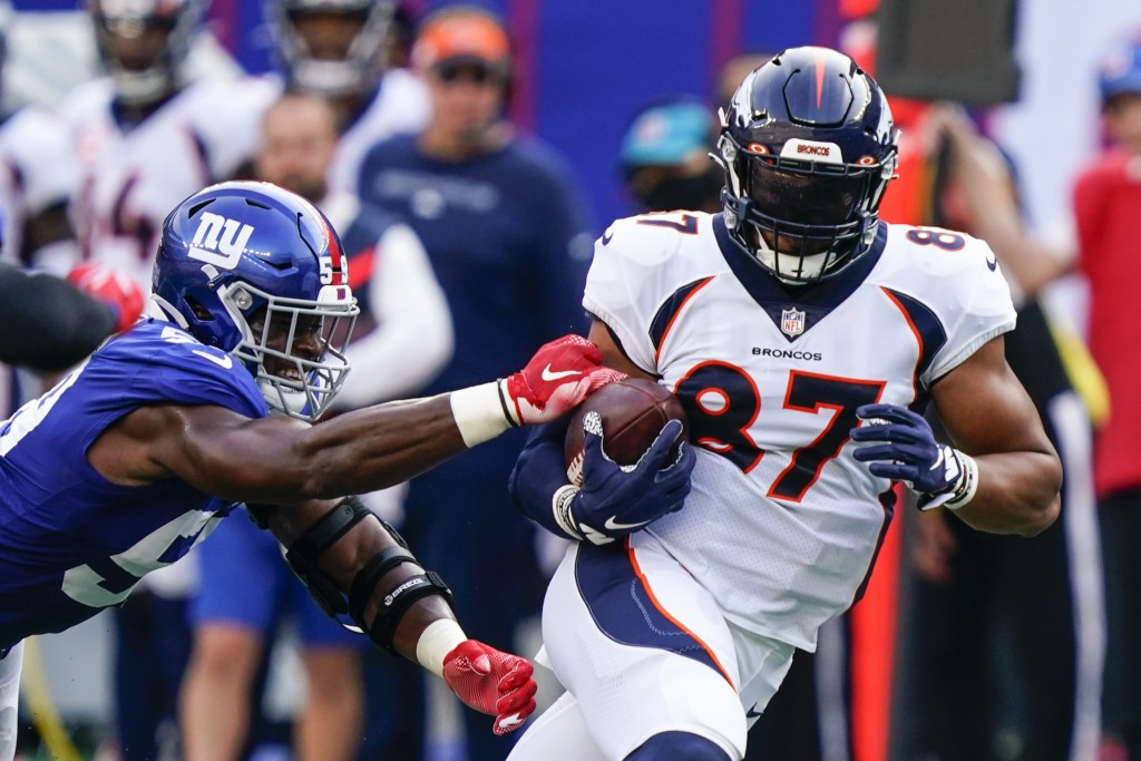 Denver Broncos tight end Noah Fant (87) protects the ball from New York Giants' Lorenzo Carter (59) during the first half of an NFL football game Sund...