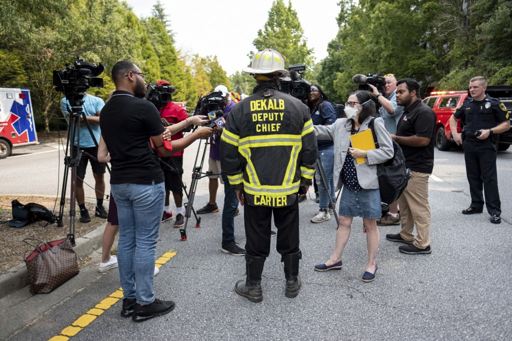 DeKalb County Fire Rescue Deputy Chief Melvin Carter briefs journalists as emergency workers respond following an apartment explosion, Sunday, Sept. 1...