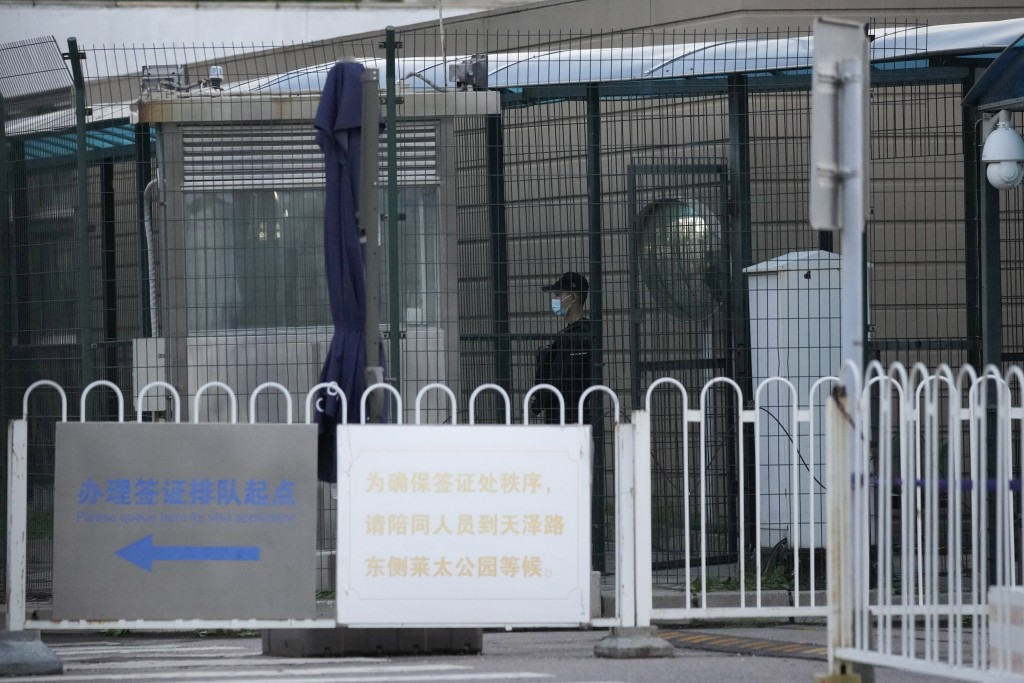 A security guard stands guard behind fences around the U.S. embassy near a sign board directing visa applicants in Beijing on Sept. 6, 2021. The Chine...