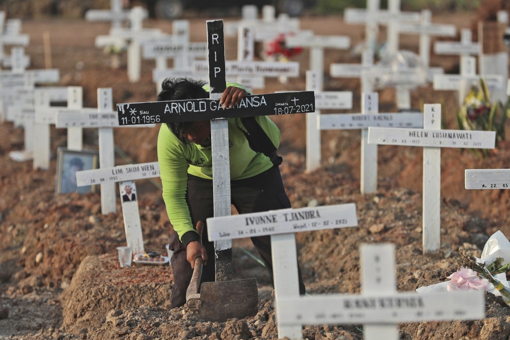 A worker fixes grave mark at Rorotan Cemetery which was reserved for those who died of COVID-19, in Jakarta, Indonesia, Wednesday, Aug. 25, 2021. Jaka...