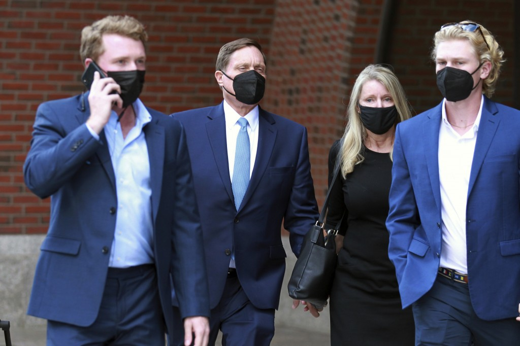 John Wilson, second left, holds his wife's hand, second right, as he leaves the John Joseph Moakley Federal Courthouse after the first day of his tria...