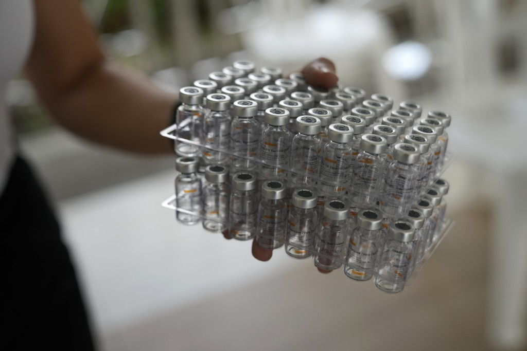 A health worker carries used bottles of China's Sinovac COVID-19 vaccine in Quezon city, Philippines on Monday, Sept. 13, 2021. The government continu...