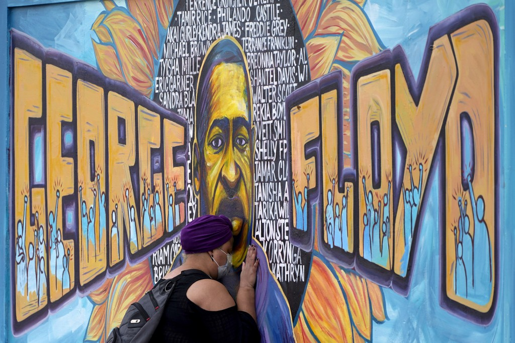 FILE - In this April 23, 2021, file photo, Damarra Atkins pays her respects to George Floyd at a mural at George Floyd Square, in Minneapolis. A fund ...