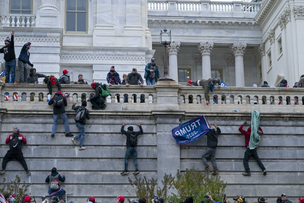 FILE - In this Jan. 6, 2021 file photo, rioters climb the west wall of the the U.S. Capitol in Washington. First, some blamed the deadly Jan. 6 attack...