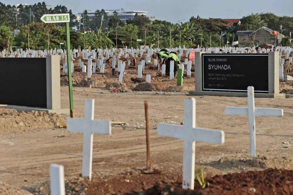Workers tidy up at the Muslim section of Rorotan Cemetery which is dedicated for COVID-19 victims, in Jakarta, Indonesia, Wednesday, Aug. 25, 2021. Th...