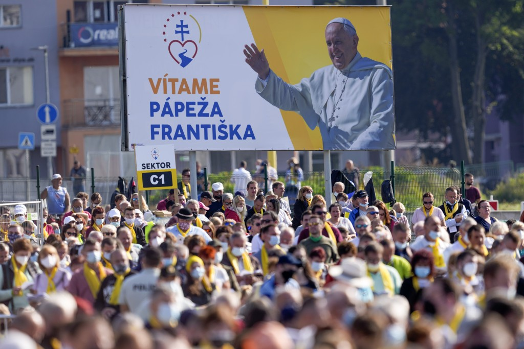 """A billboard with writing reading in Slovak """"Welcome Pope Francis"""" is seen behind faithful attending a Byzantine rite Mass celebrated by Pope Francis a..."""