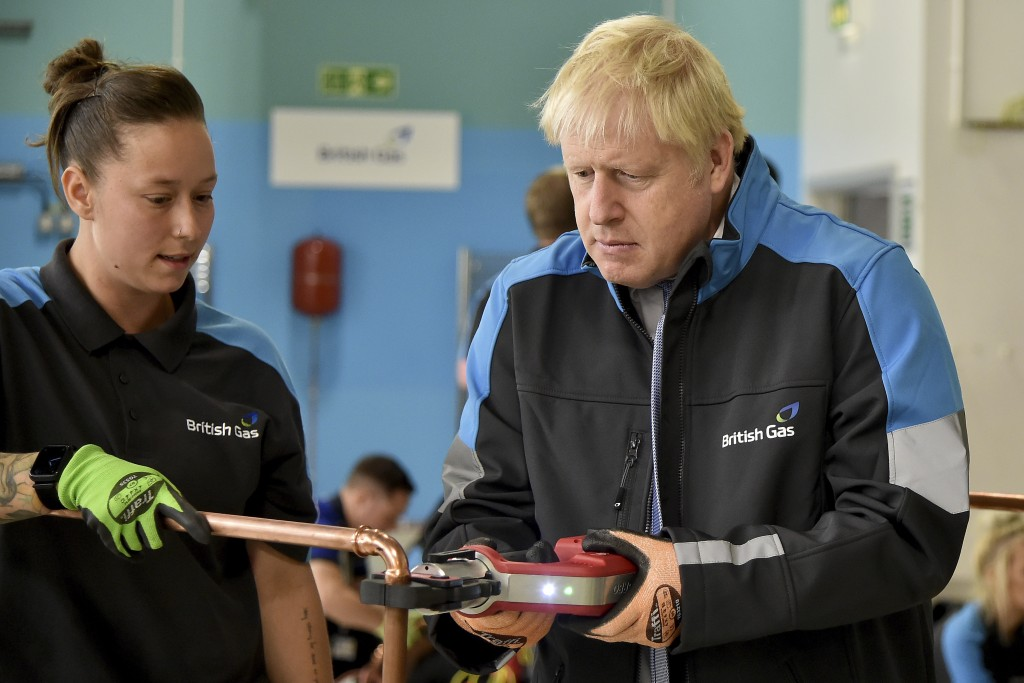 Britain's Prime Minister Boris Johnson listens to apprentice Amy Gray during a visit to a British Gas training academy in Leicestershire, England, Mon...