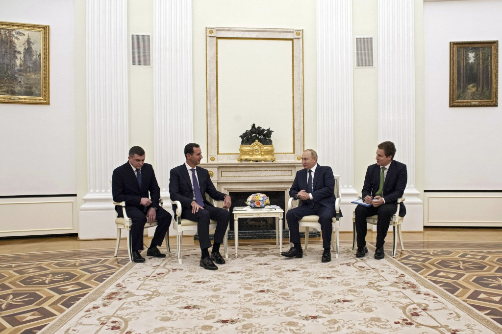 Russian President Vladimir Putin, second right, speaks to Syrian President Bashar Assad during their meeting in the Kremlin in Moscow, Russia, Monday,...