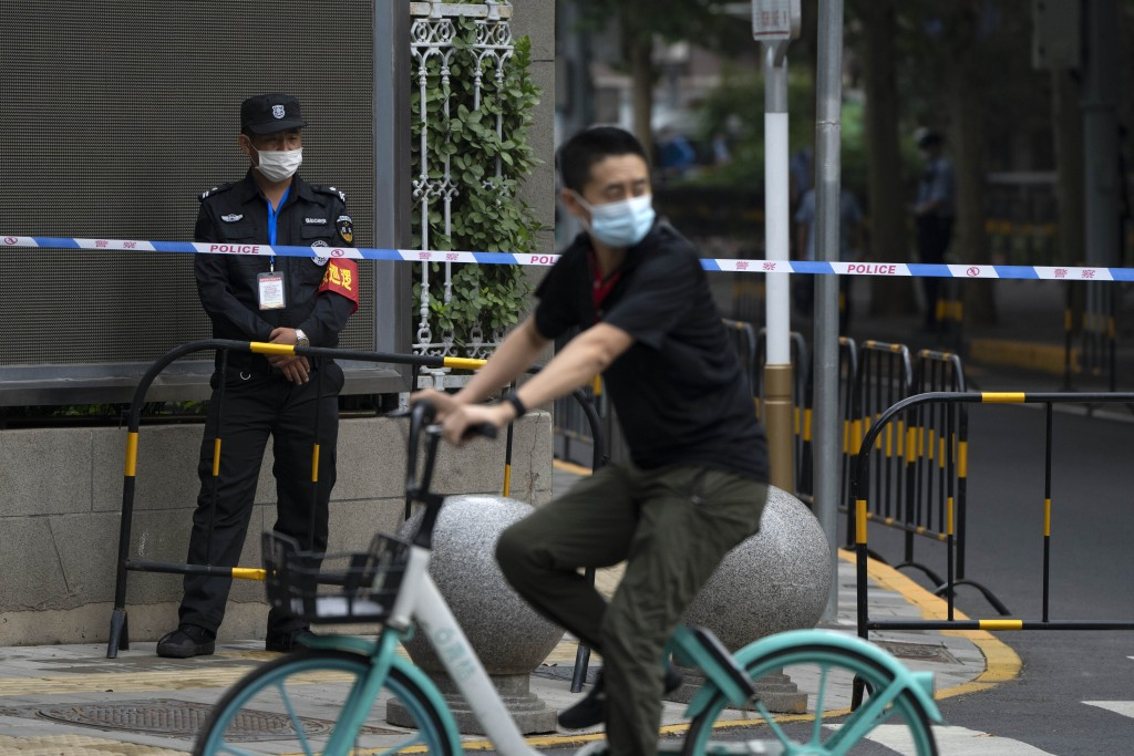 A security office stands guard at a barricade outside a courthouse in Beijing, Tuesday, Sept. 14, 2021. A young Chinese woman headed to court Tuesday ...