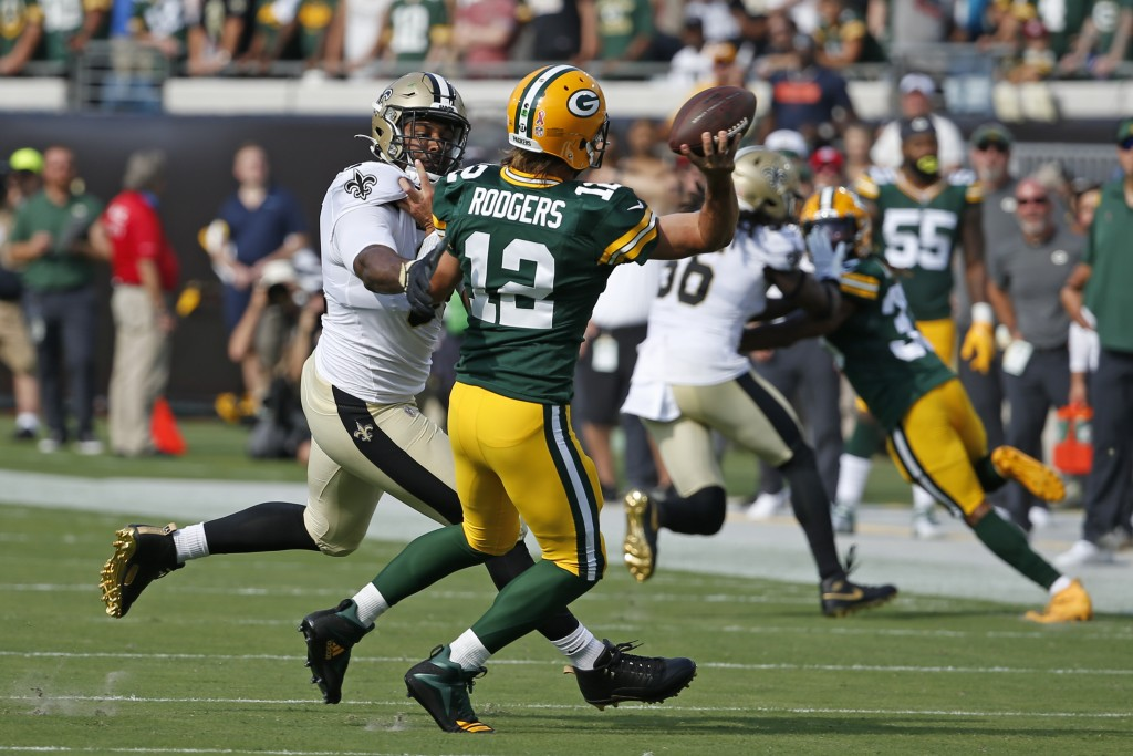 Green Bay Packers quarterback Aaron Rodgers (12) is his by New Orleans Saints defensive end Cameron Jordan, left, as he releases a pass during the fir...