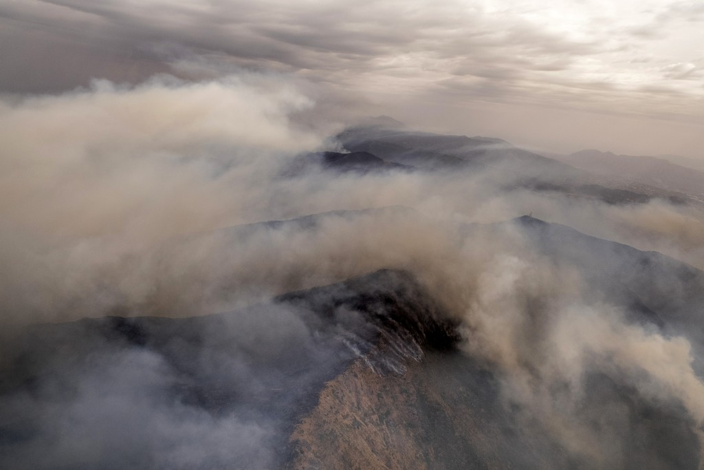Smoke rises over smoke filled mountains near the town of Jubrique, in Malaga province, Spain, Monday, Sept. 13, 2021 Firefighting crews in southern Sp...