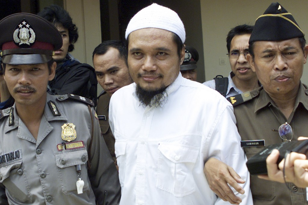FILE - Militant cleric Abu Rusdan, center, is escorted by security officers after his trial hearing at a district court in Jakarta, Indonesia, in this...