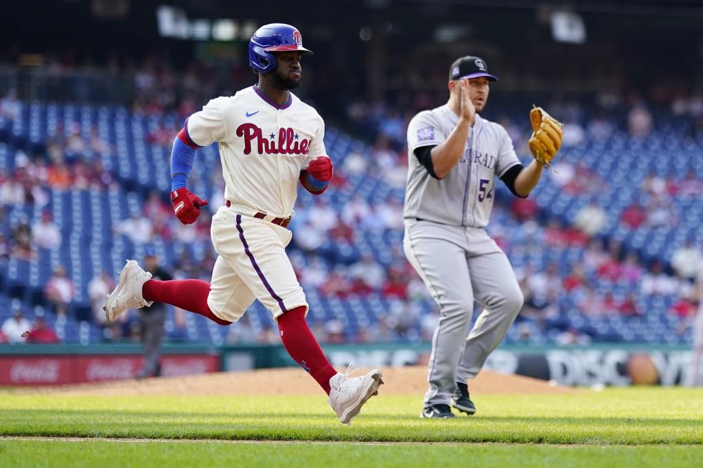 Philadelphia Phillies' Odubel Herrera, left, and Colorado Rockies' Carlos Estevez react as Herrera grounds out to end a baseball game, Sunday, Sept. 1...