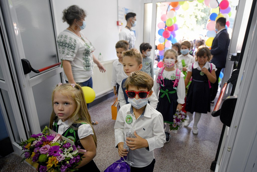 Children wearing face masks enter a school at the end of festivities marking the beginning of the school year, in Bucharest, Romania, Monday, Sept. 13...