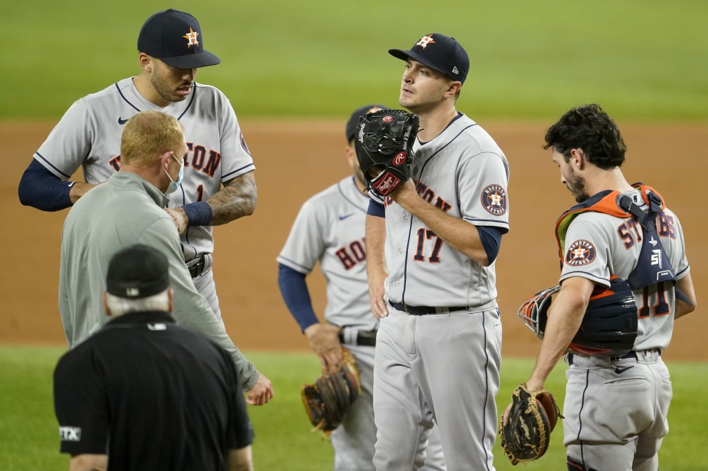 Houston Astros starting pitcher Jake Odorizzi (17) stands on the mound as umpire Larry Vanover, a team staff member, left, Carlos Correa, left rear, a...