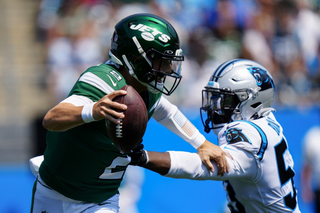 New York Jets quarterback Zach Wilson pushes away Carolina Panthers defensive end Brian Burns during the first half of an NFL football game Sunday, Se...