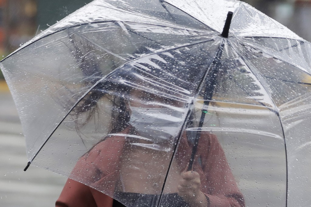 A woman struggles with her umbrella against powerful gusts of wind generated by Typhoon Chanthu in Taipei, Taiwan, Sunday, Sept. 12, 2021. Typhoon Cha...
