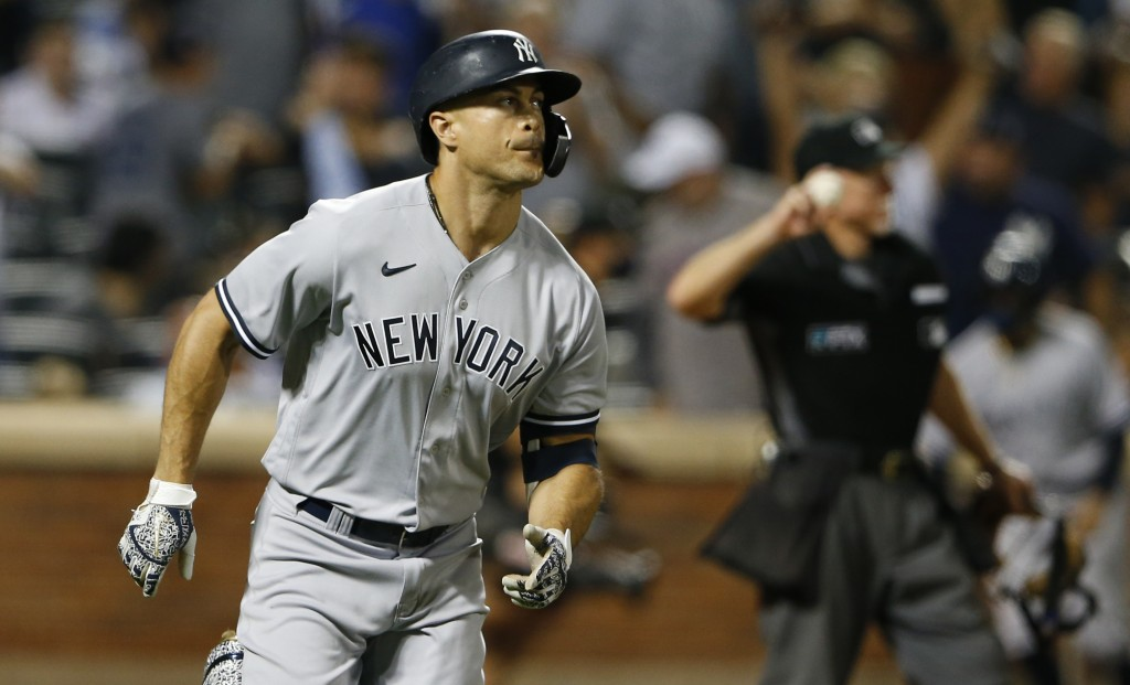 New York Yankees' Giancarlo Stanton rounds the bases after hitting a home run during the seventh inning of a baseball game against the New York Mets, ...