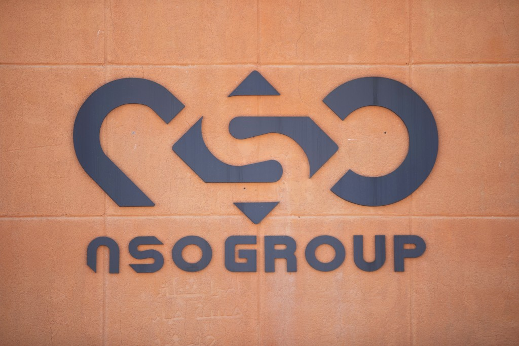 FILE - In this Tuesday, Aug. 24, 2021, file photo, a logo adorns a wall on a branch of the Israeli NSO Group company, near the southern Israeli town o...