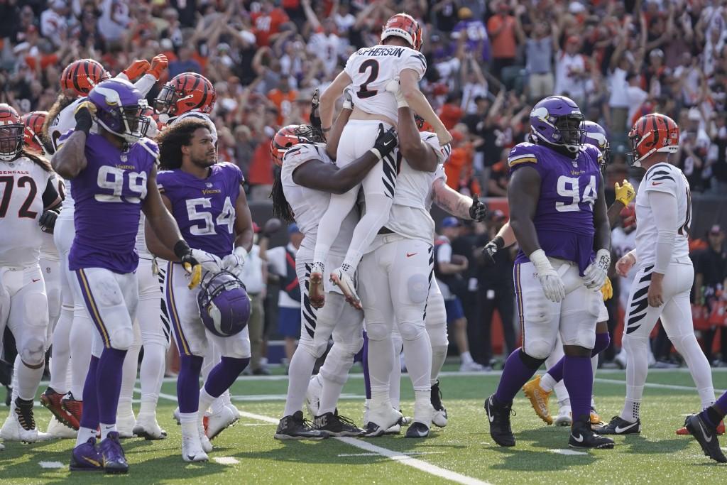 The Minnesota Vikings walk off the field as the Cincinnati Bengals hoist their kicker Cincinnati Bengals kicker Evan McPherson (2) after he made a fie...