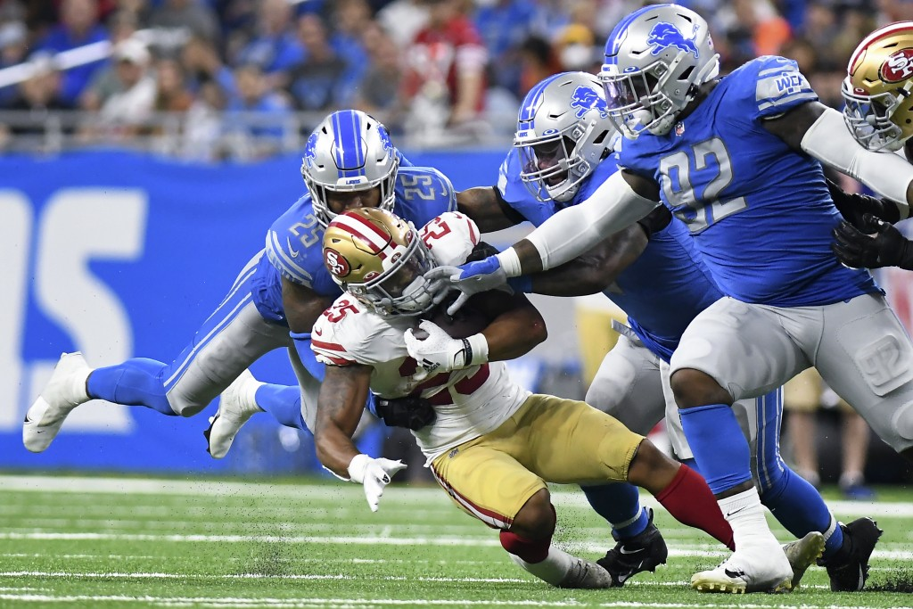 San Francisco 49ers running back Elijah Mitchell (25) is brought down by Detroit Lions cornerback Jeff Okudah (23) in the second half of an NFL footba...