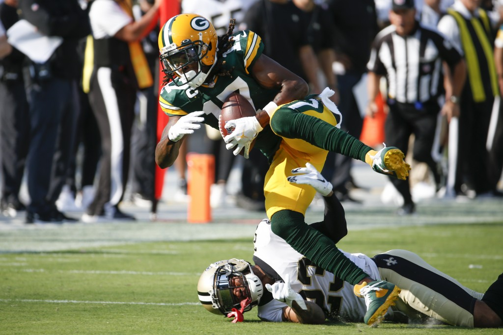 Green Bay Packers wide receiver Davante Adams (17) catches a pass as New Orleans Saints cornerback Marshon Lattimore, lower left, tries to stop him du...