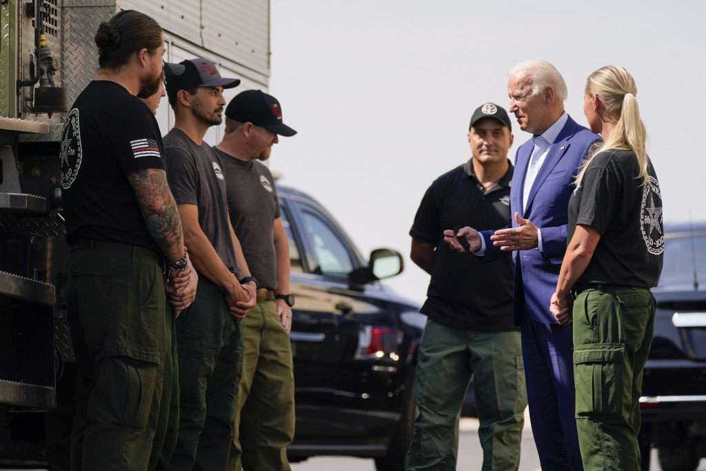 President Joe Biden greets firefighters as he tours the National Interagency Fire Center, Monday, Sept. 13, 2021, in Boise, Idaho. (AP Photo/Evan Vucc...