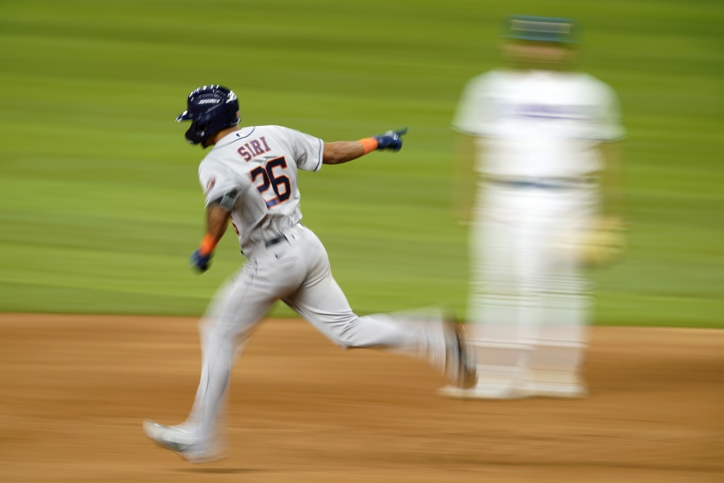 Houston Astros' Jose Siri (26) celebrates his solo home run as he rounds the bases past Texas Rangers first baseman Nathaniel Lowe in the eighth innin...