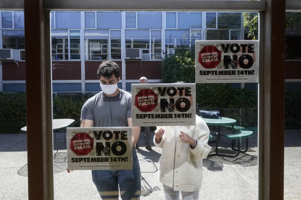 Volunteers put up signs to Vote No on recalling Gov. Gavin Newsom in San Francisco, Tuesday, Sept. 14, 2021. The recall election that could remove Cal...