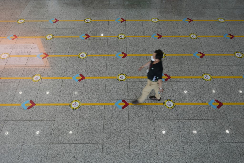 A visitor wearing a face mask to help curb the spread of the coronavirus walks across markings displayed on the floor for the social distancing measur...