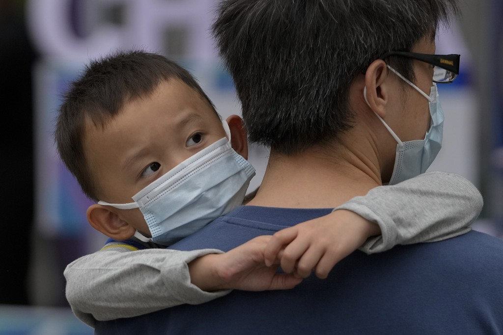 A man carries a child, both wearing face masks to help curb the spread of the coronavirus, walk on a street in Beijing, Sunday, Sept. 12, 2021. (AP Ph...