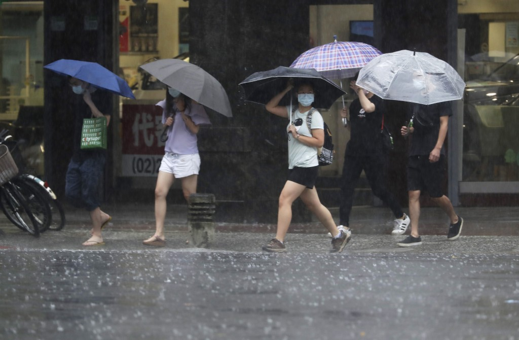 People walk in the rain caused by Typhoon Chanthu in Taipei, Taiwan, Sunday, Sept. 12, 2021. Typhoon Chanthu drenched Taiwan with heavy rain Sunday as...