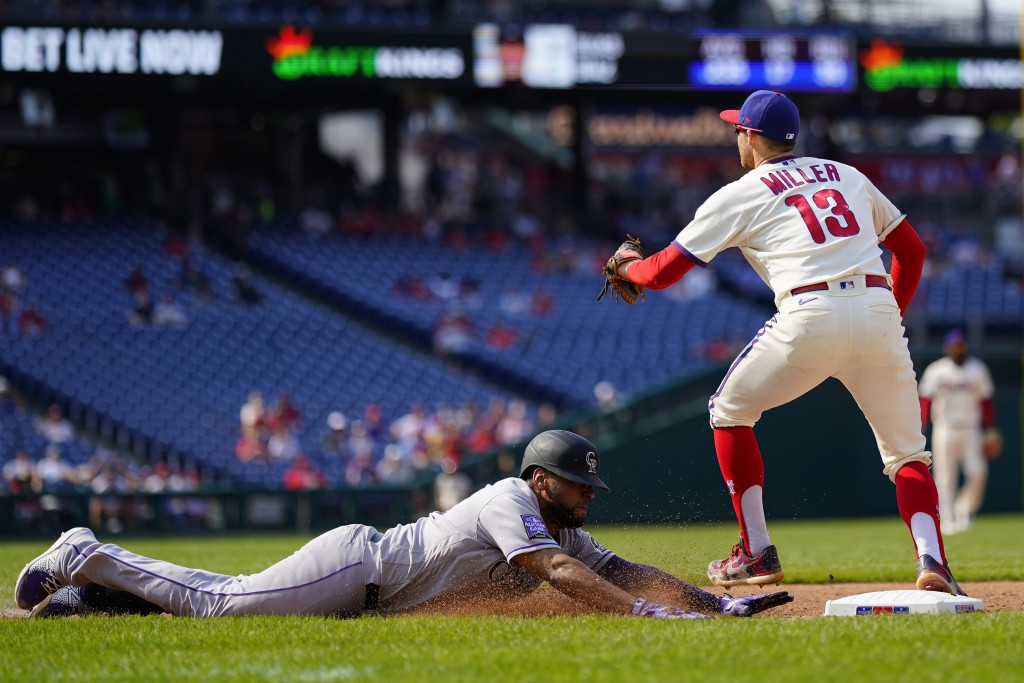 Colorado Rockies' Elias Diaz, left, slides into first base for a single past Philadelphia Phillies first baseman Brad Miller during the seventh inning...