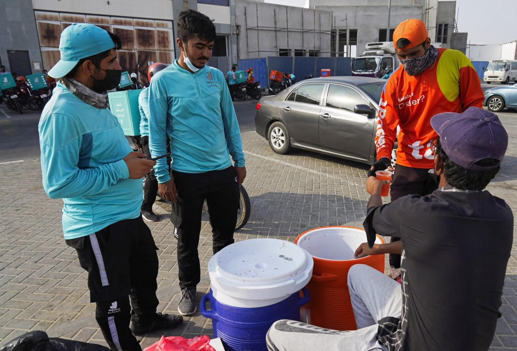 Motorcycle delivery drivers take a break and buy juice, in Dubai, United Arab Emirates, Thursday, Sept. 9, 2021. Advocates and workers say that casual...
