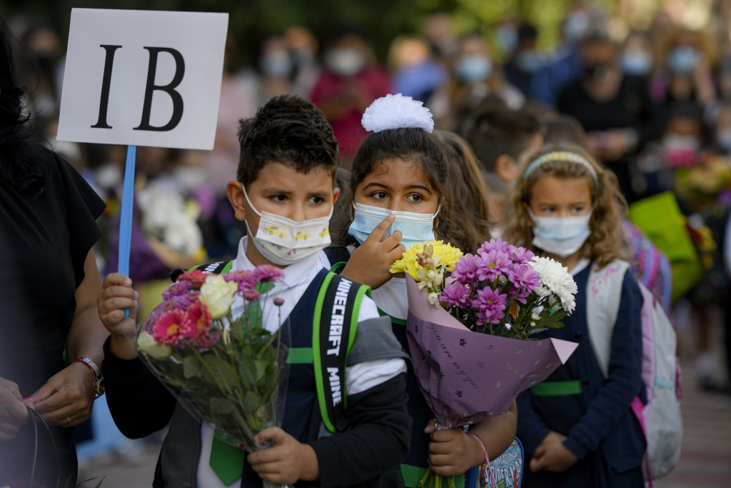 Children wearing face masks hold flowers during festivities marking the beginning of the school year at a school in Bucharest, Romania, Monday, Sept. ...