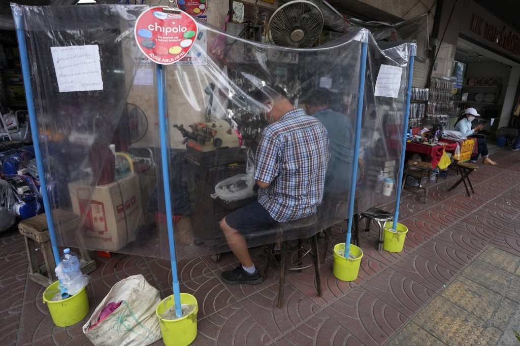 Two locksmiths provide services to customers from behind protective plastic sheets to help curb the spread of the COVID-19 in Bangkok, Thailand, Tuesd...