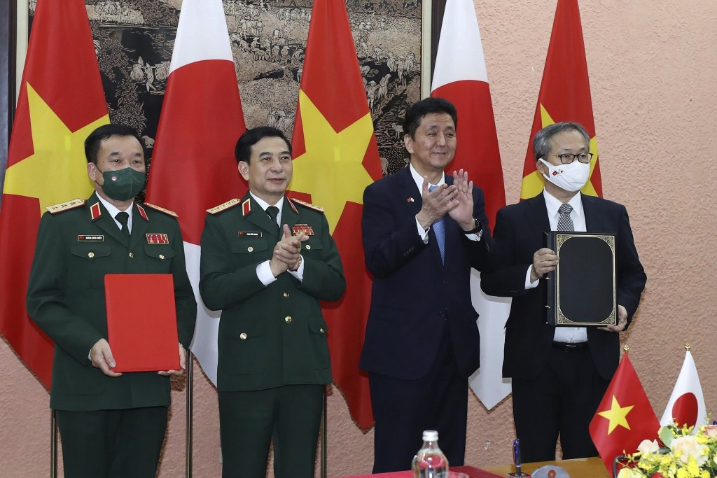 Vietnamese Defense Minister Phan Van Giang, center left, and Japanese Defense Minister Nobuo Kishi, center right, stand for photo with their officials...