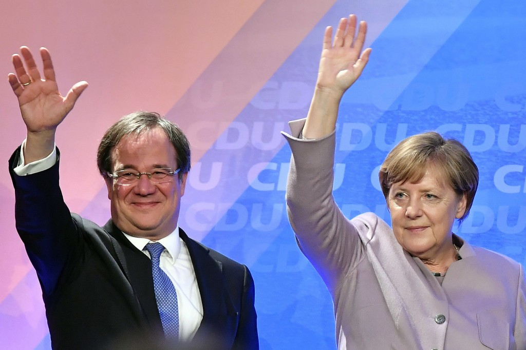 FILE - In this Thursday, April 27, 2017 file photo Christian Democrats chancellor candidate Armin Laschet and German chancellor Angela Merkel wave to ...