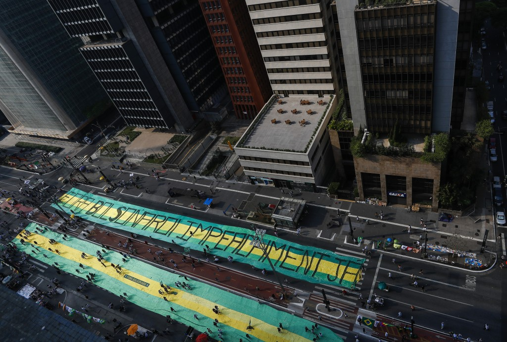 """Opposition groups extend a giant banner that reads in Portuguese """"Bolsonaro Get Out, Impeachment now,"""" during a protest against Brazilian President Ja..."""