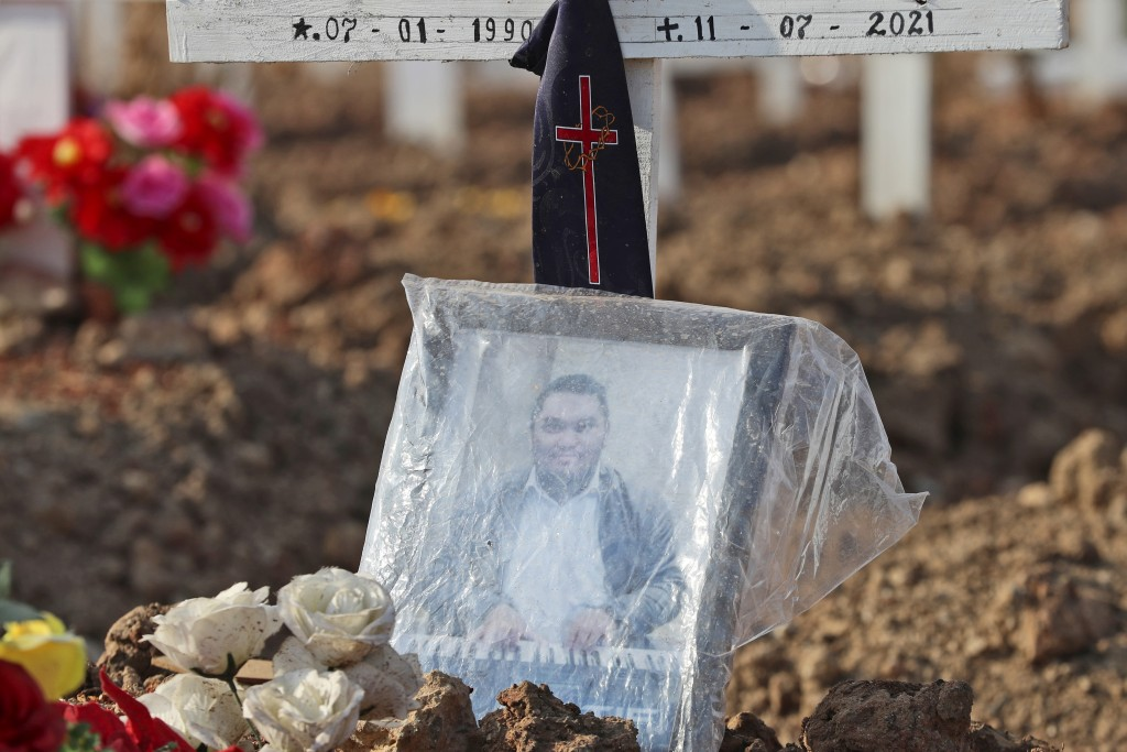 A photograph is placed on the grave of a man who died of COVID-19 at Rorotan Cemetery in Jakarta, Indonesia, Wednesday, Sept. 1, 2021. Family members ...