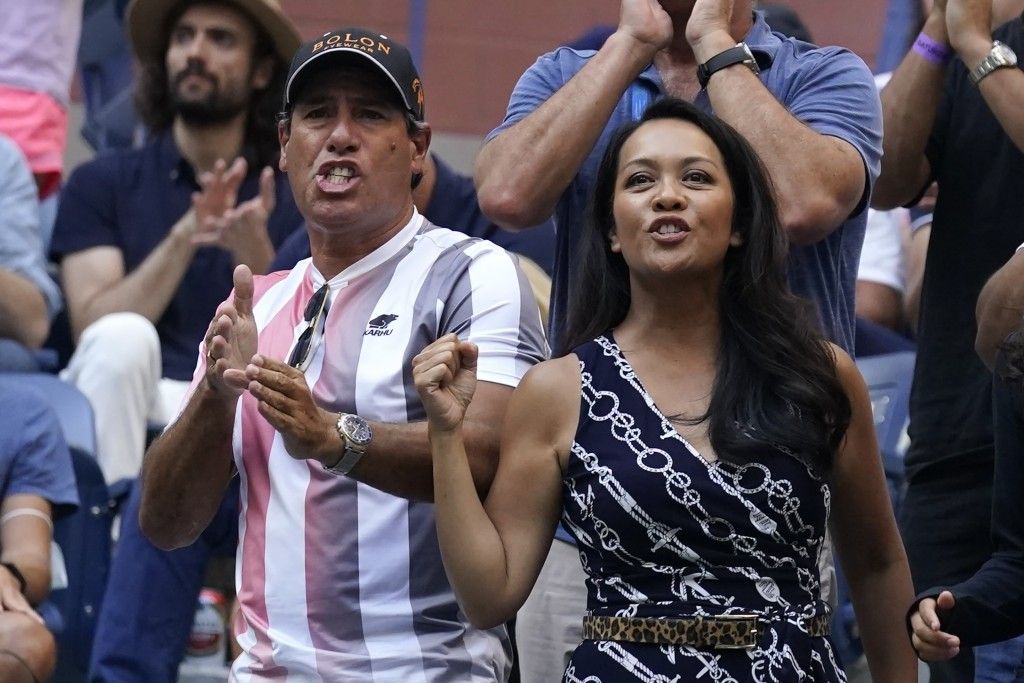 Duglas Cordero, left, fitness coach for Leylah Fernandez, of Canada, and Irene Exevea, Fernandez's mother, cheer her on during the women's singles fin...