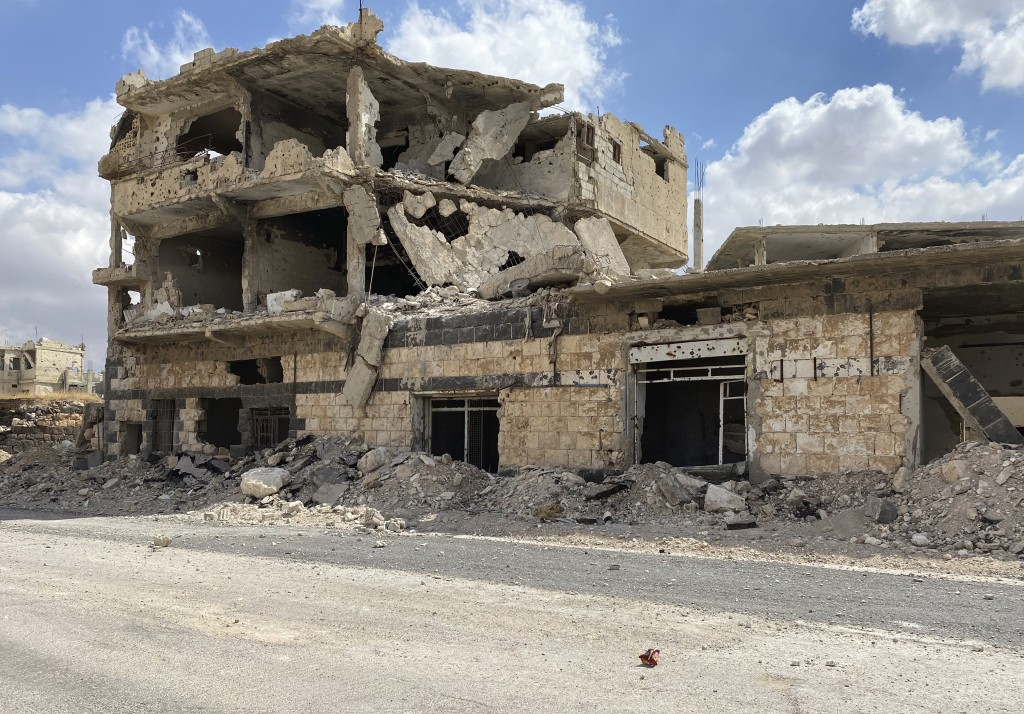 A building damaged by Syrian government forces following clashes with rebel fighters is seen in the southern city of Daraa, Syria, Sunday, Sept 12, 20...