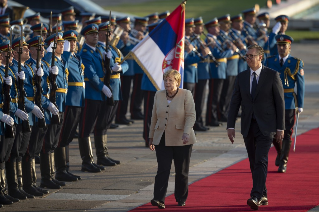 German Chancellor Angela Merkel, center, walks past honor guards while being accompanied by Serbia's president Aleksandar Vucic, front left, in Belgra...